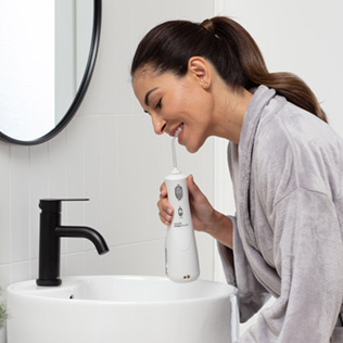 Woman using the WP-450 Cordless Advanced Water Flosser